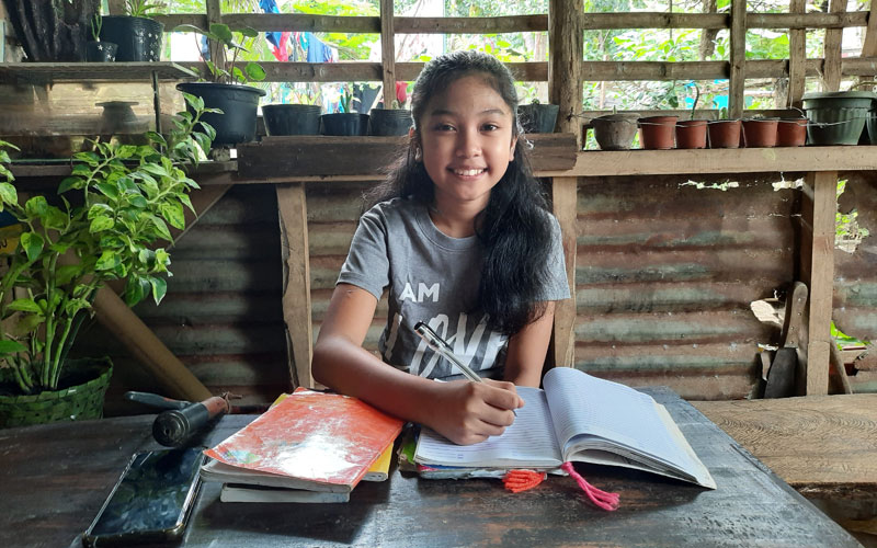 a young Filipina girl sits at a table with books open in front of her.