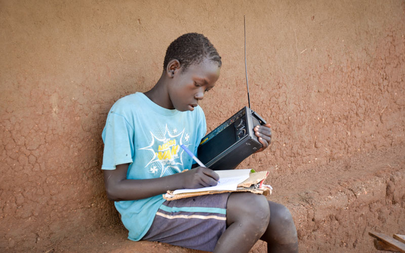 a young South Sudanese boy listens to a radio and writes in a notebook.