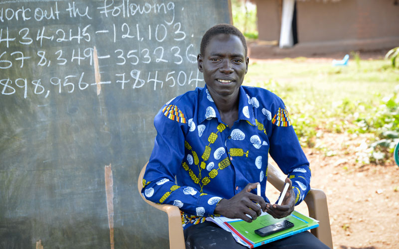 A South Sudanese man sits in front of a chalkboard