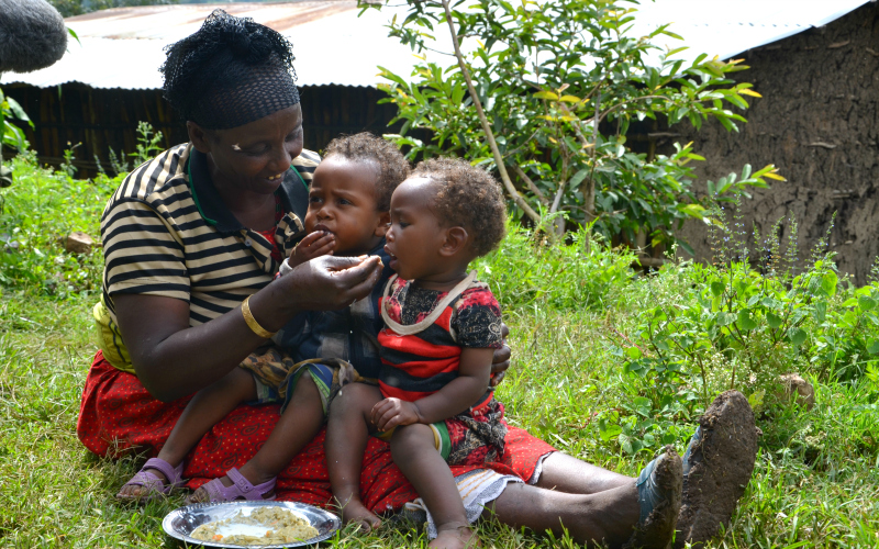 A woman holds two little children on her lap and feeds them
