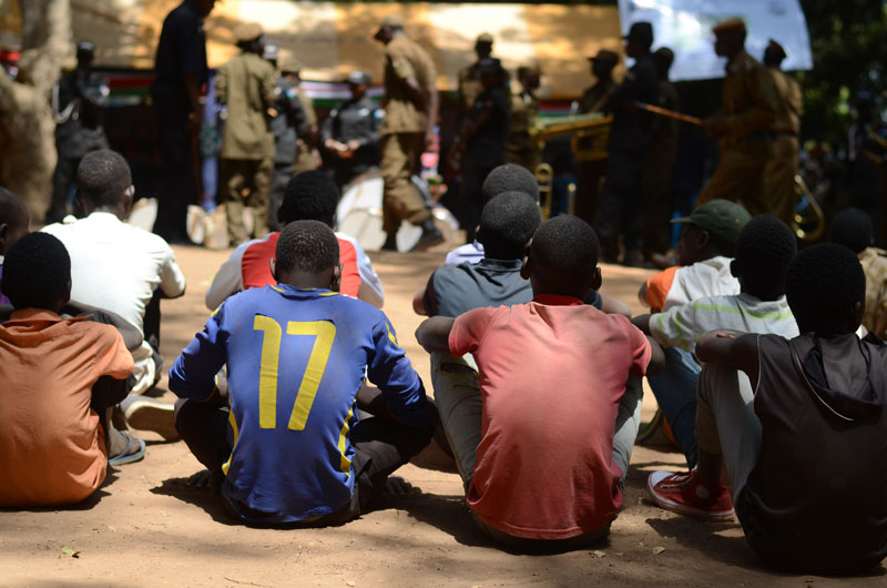 Former child soldier teenage boys appear sitting on a dirt ground with their backs to the camera, waiting to receive assistance.