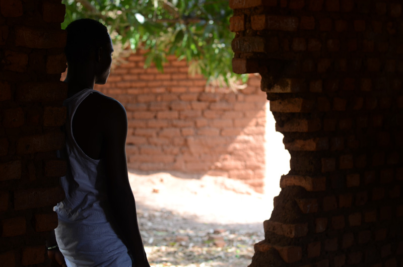 A young man, former child soldier in South Sudan, leans against a broken brick wall.