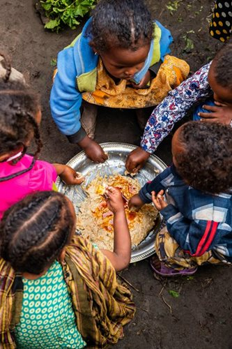 A group of children eat around a common bowl.