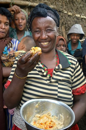 A smiling woman holds up maqua from a bowl, her friends behind her